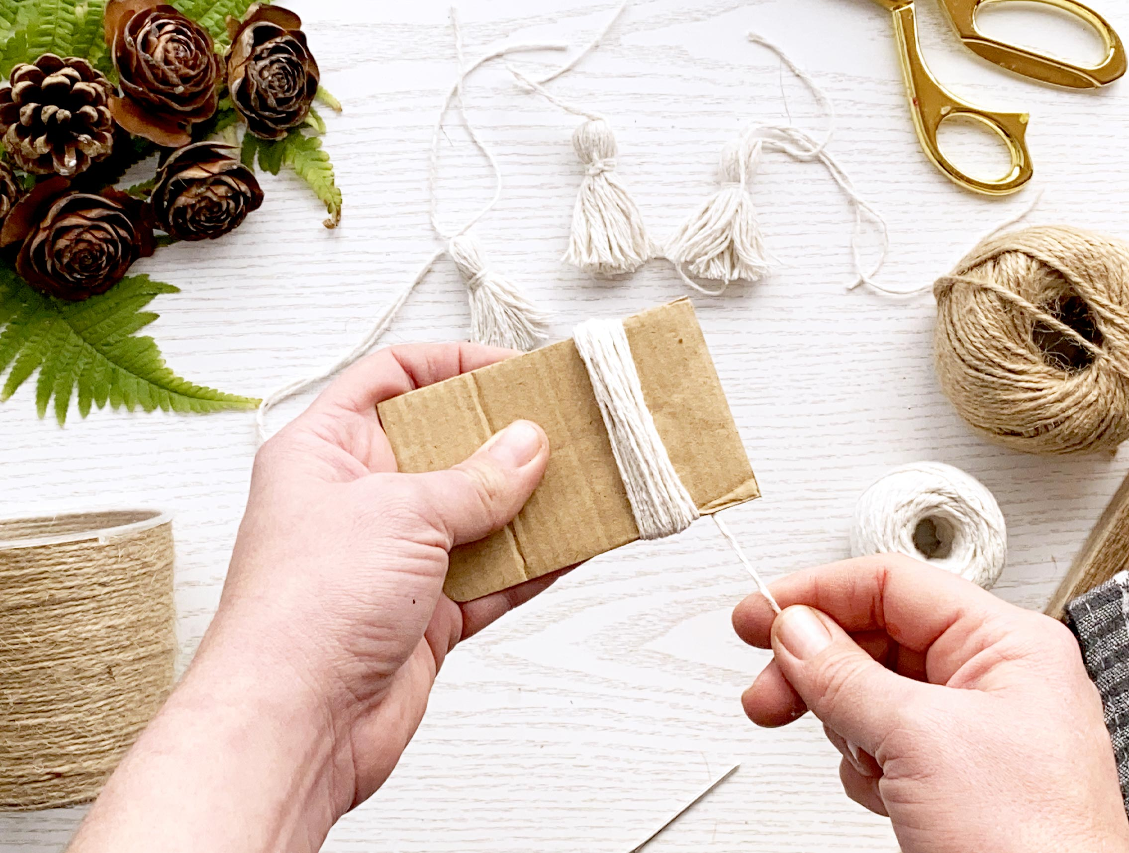 make your tassels – do this by taking a 7cm thick piece of card, and wrap the white string around it about 30 times.