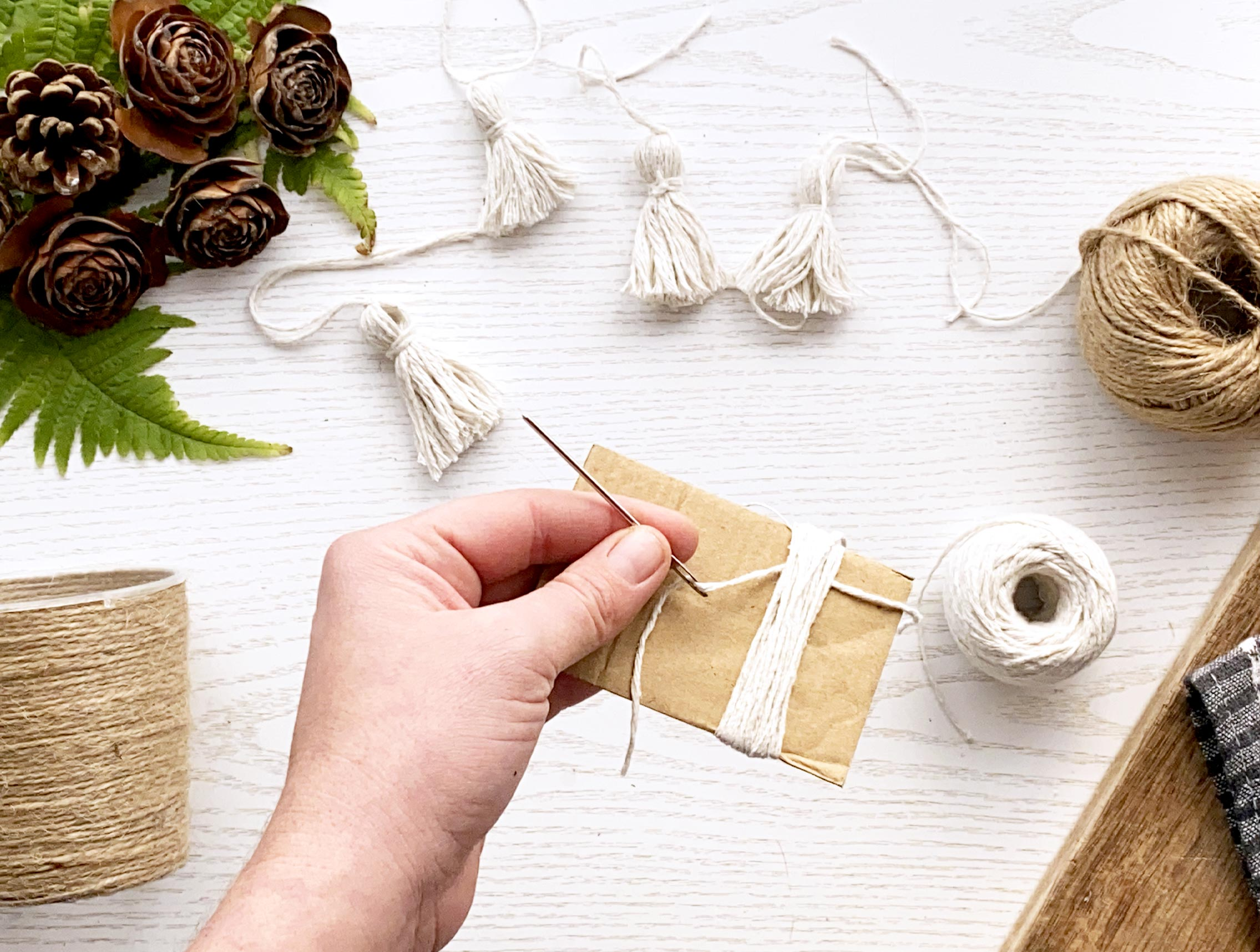 Needle pulling thread througn string wrapped around cardboard to create tassel